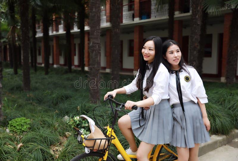 Relaxe o estudante que bonito chinês asiático do desgaste das meninas o terno na escola aprecia a bicicleta do passeio do tempo l imagem de stock royalty free