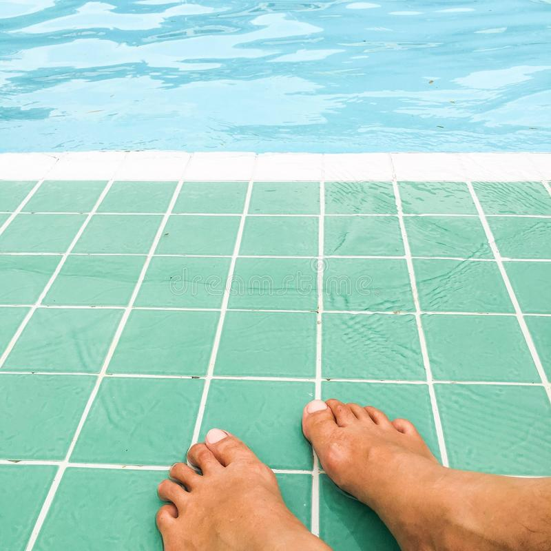 Relaxe o tempo na piscina, pés na água fotografia de stock