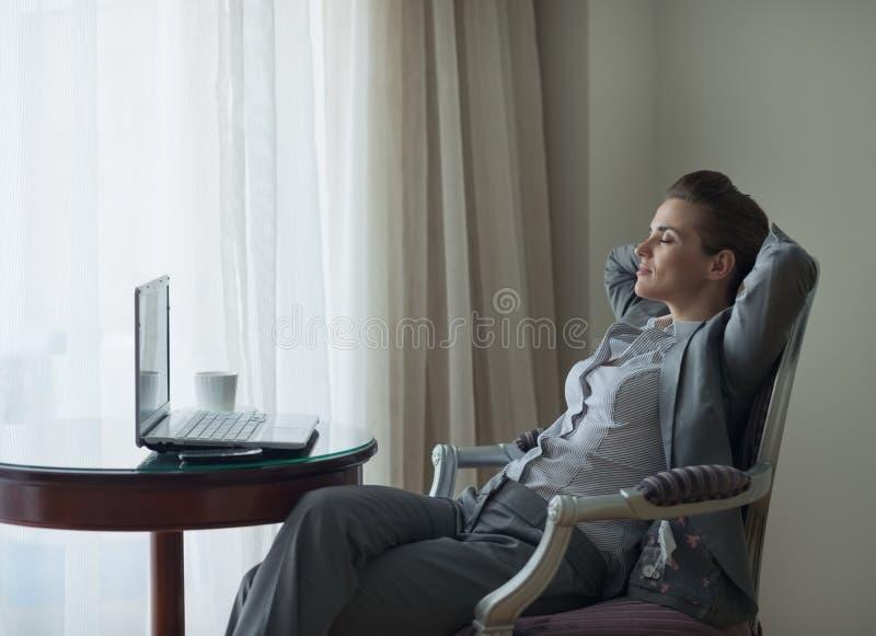 Relaxed женщина дела сидя в стуле в комнате стоковое фото rf