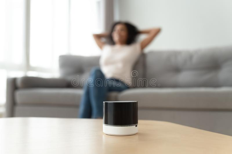 Relaxed African American woman listening to music on portable speaker royalty free stock images