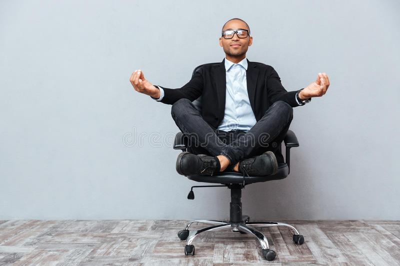 Relaxed african young man sitting and meditating on office chair. Relaxed handsome african young man sitting and meditating on office chair stock photography