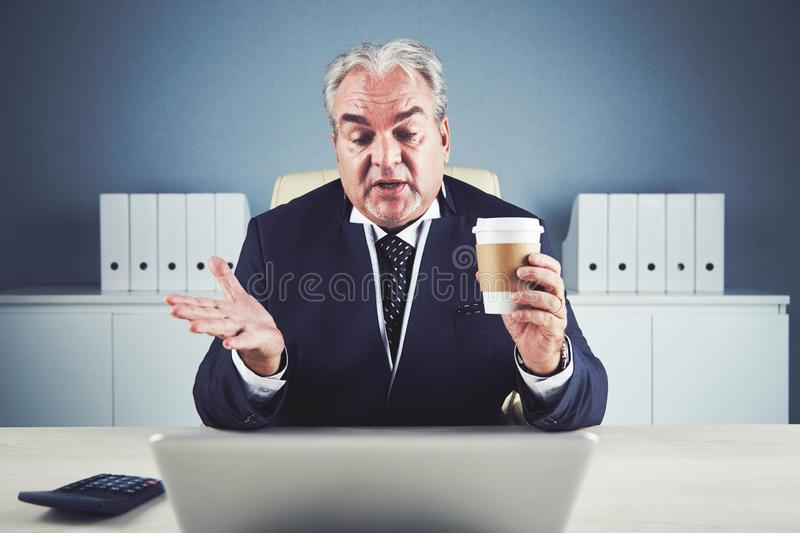 Relaxed aged businessman with beverage video chatting stock image