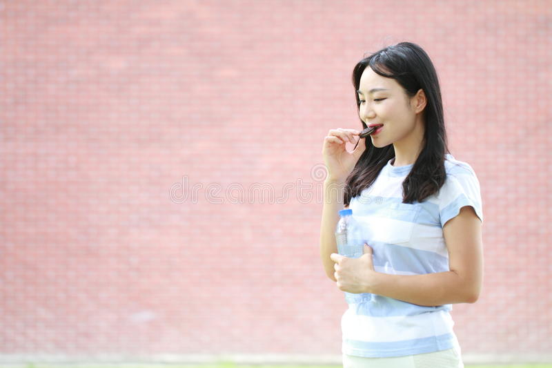 Relaxed Asian Chinese girl enjoy free time,eat snack. Asian Chinese woman enjoy free time at school, hold a bottle of water, and carry a piece of biscuit in royalty free stock photography