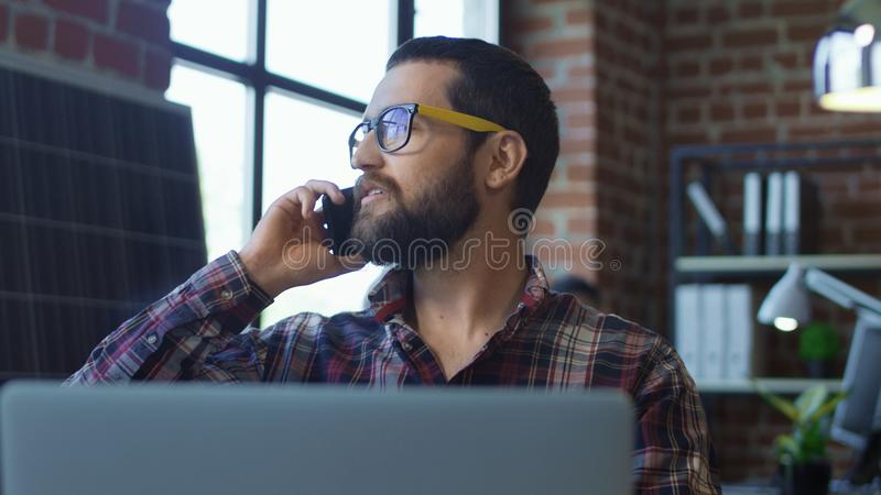 Bearded man speaking on phone in office royalty free stock photography