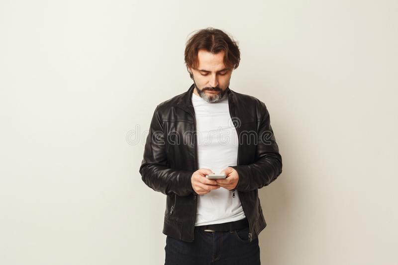 Relaxed bearded man typing message on smartphone stock image