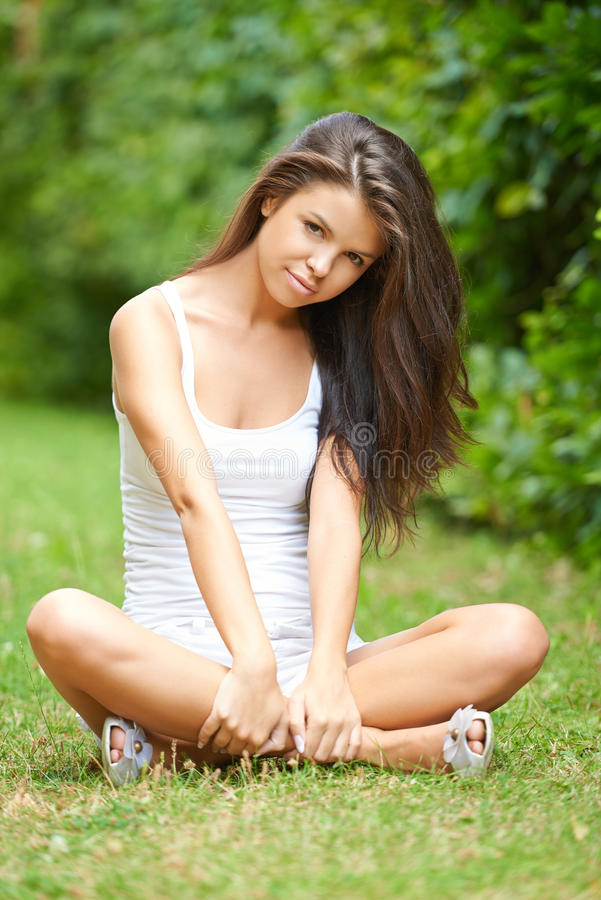 Download Relaxed Beautiful Brunette Sitting On Grass Stock Photo - Image of attractive, green: 33034966