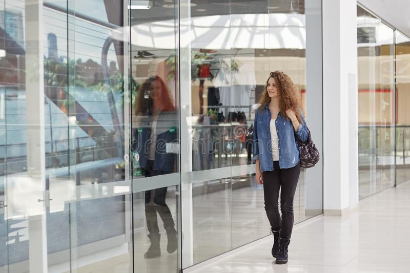 Relaxed beautiful curly woman spends day off in eneteratinng centre or shopping mall, stands in hall with glass shop windows, carr stock image