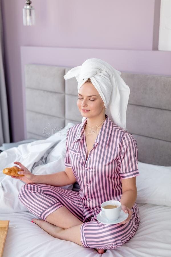 Relaxed beautiful woman doing yoga exercises while having breakfast stock image