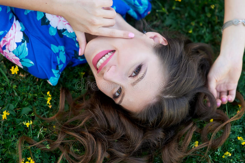 Relaxed beautiful young woman in blue dress lying on grass royalty free stock photography