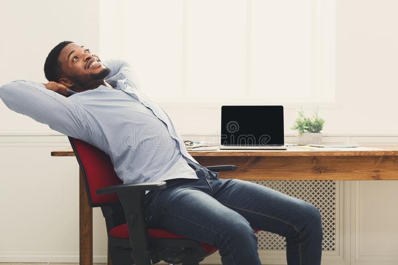 Relaxed black businessman in modern white office royalty free stock photos