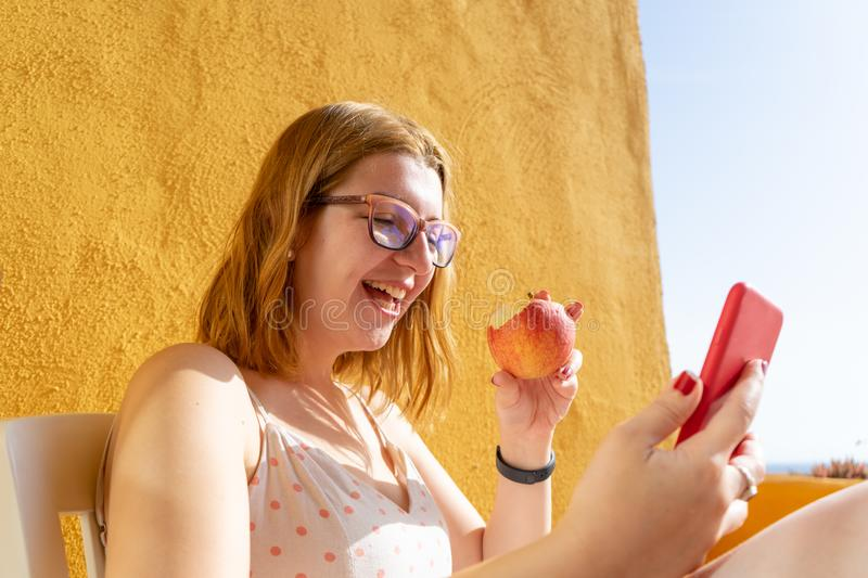 Relaxed blond teen laughing while eating a red apple, lying in the terrace of the resort and making a video call in her smart stock photos