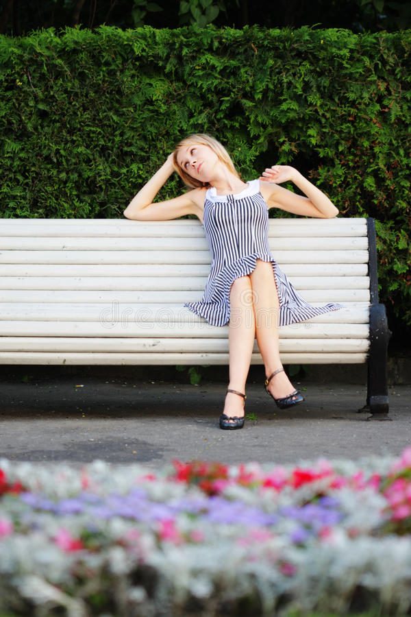 Relaxed Blonde Sitting On Bench Royalty Free Stock Photos