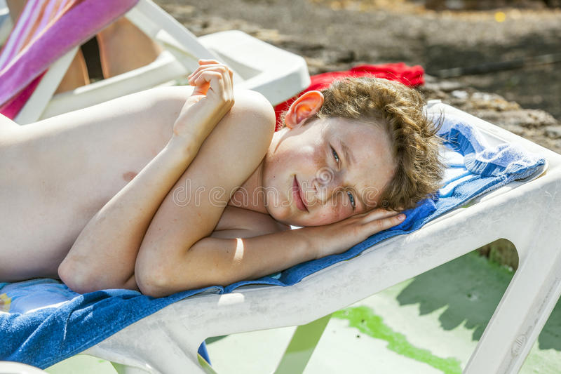 Relaxed boy enjoys lying on stock photography