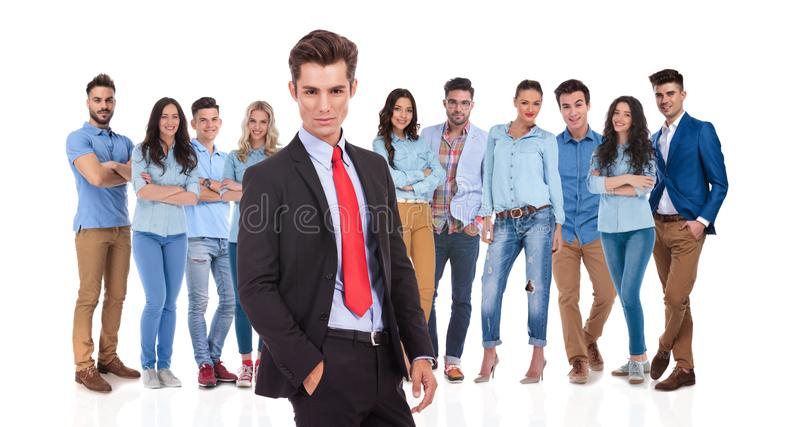 Relaxed businessman standing in front of his young casual team royalty free stock images
