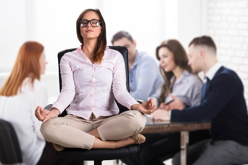 Businesswoman Meditating In Office stock images