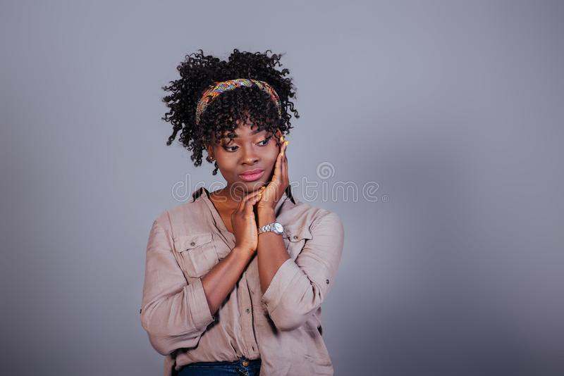 Relaxed and calm. Attractive afro american woman in casual clothes in the studio.  stock photography