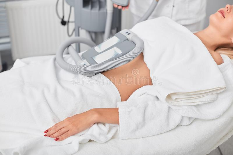 Relaxed calm woman taking treatment in the clinic. Close up cropped side view photo. machine for weight loss stock photo