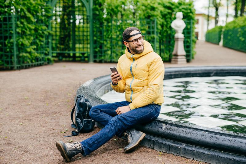 Relaxed carefree bearded traveler male in trendy cap, anorak, jeans and eyewear having excursion in forest reserve sitting near fo royalty free stock photos