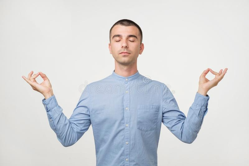 Relaxed carefree male student meditates tries to relax after long hours of studying, concentrates on something royalty free stock images