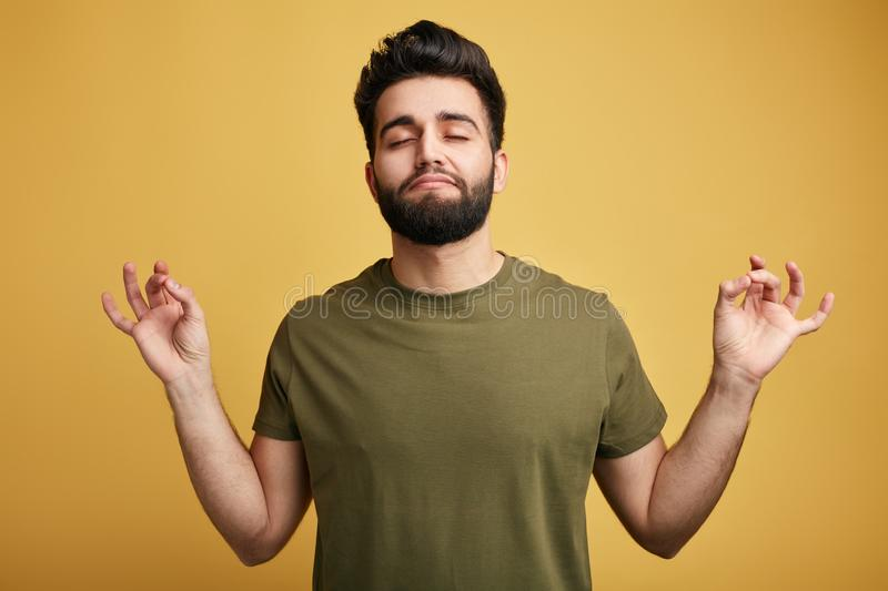 Relaxed carefree man tries to relax after hard working day, mediates and shuts eyes, enjoys calm and peaceful atmosphere. Man tries to relax after hard working stock image