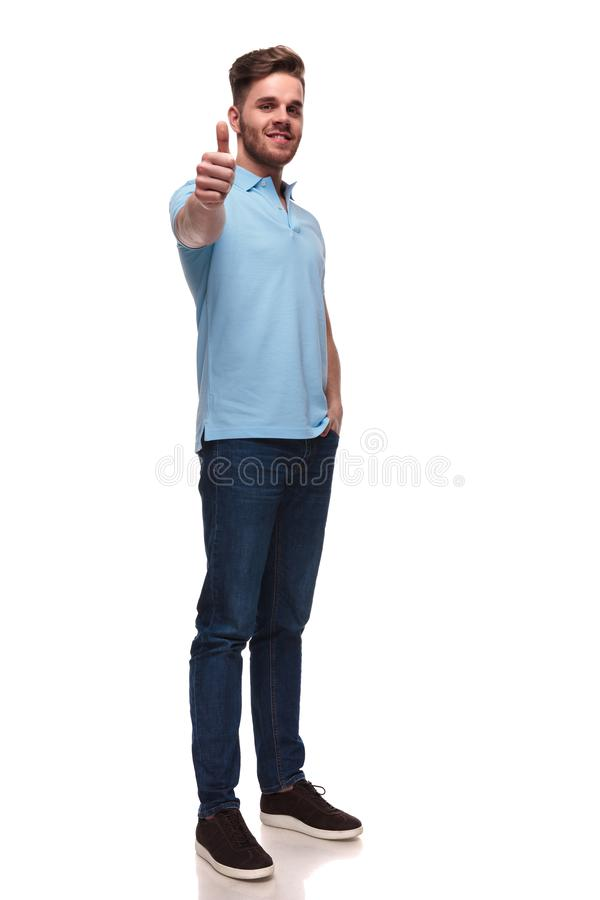 Relaxed casual man in polo shirt makes ok sign. While standing on white background with a hand in pocket, full length picture royalty free stock photo