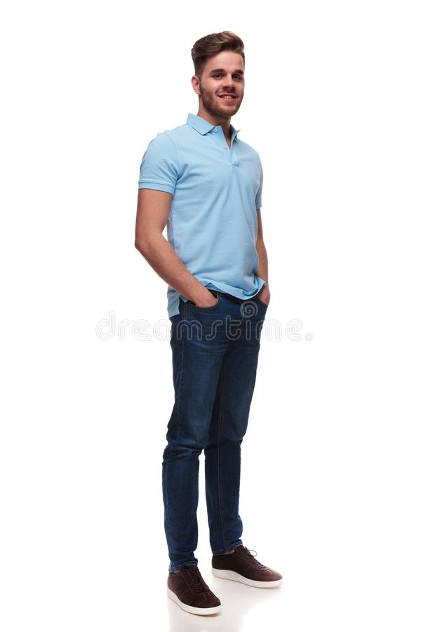 Relaxed casual man in polo shirt standing and holding pockets. Relaxed casual man in polo shirt standing on white background and holding pockets, full body stock image