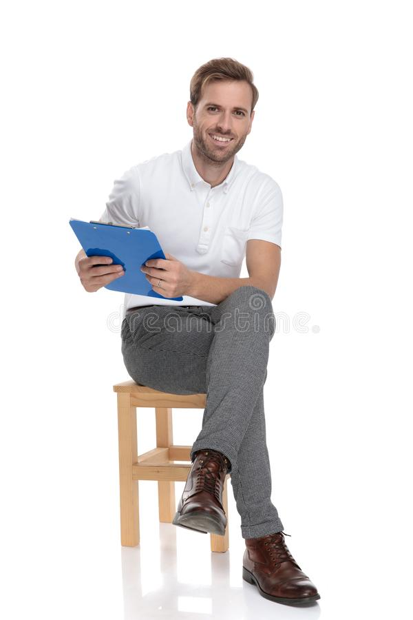 Relaxed casual man sitting and holding a blue clipboard royalty free stock photo