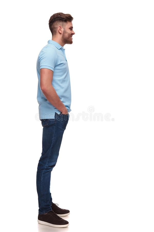 Relaxed casual man wearing polo shirt waiting in line. And smiling while standing on white background, full length picture stock image