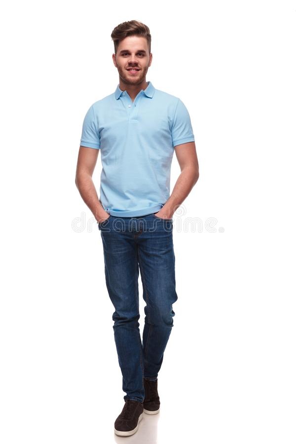 Relaxed casual man wearing a polo shirt walking forward. On white background, full length picture royalty free stock images
