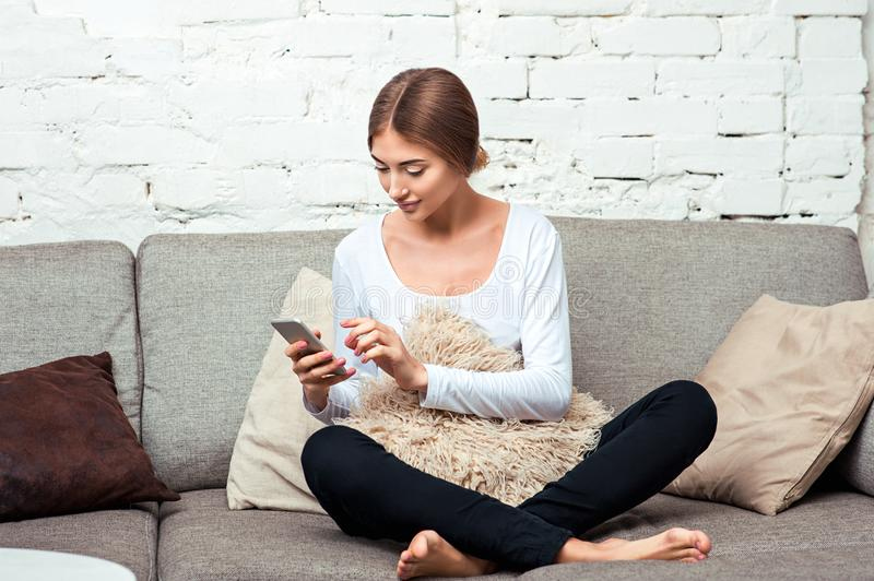 Woman with a mobile phone on couch stock photography