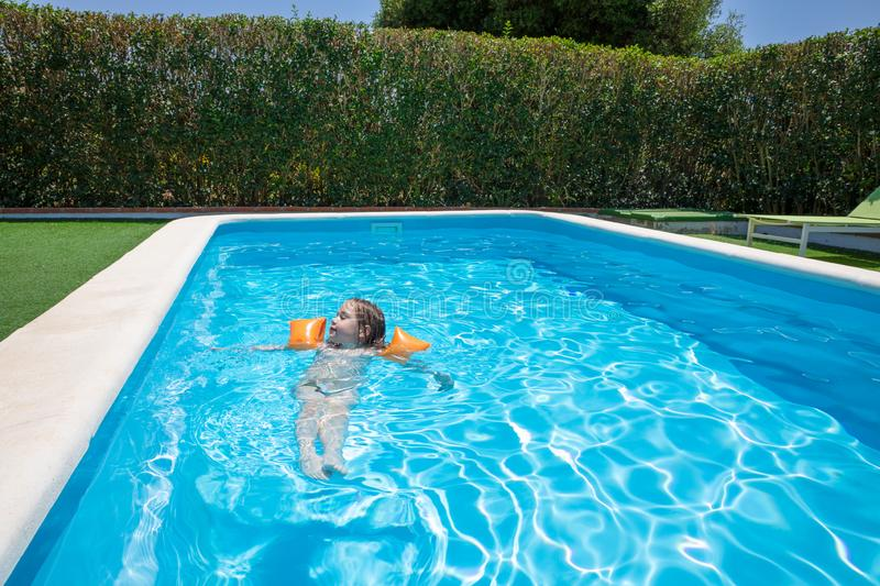 Relaxed child with armbands floating in transparent blue water of pool stock photography