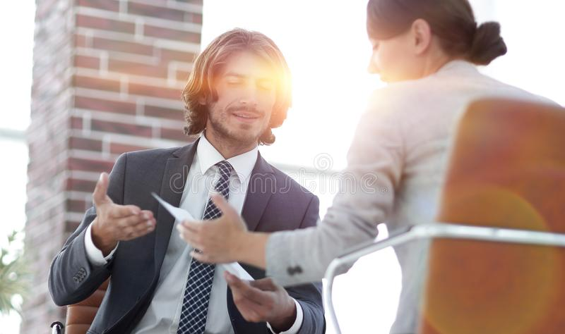 A relaxed conversation of a man and a woman in the office. Successful young consultants working as business team in an office analyzing documents stock image