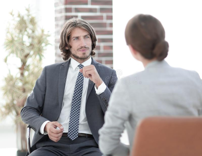 A relaxed conversation of a man and a woman in the office. Successful young consultants working as business team in an office analyzing documents royalty free stock image