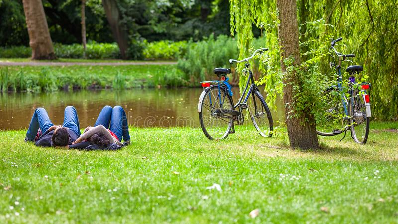 Relaxed couple on grass, Vondelpark, Amsterdam. Relaxed couple on grass in public park after a bike riding, Vondelpark, Amsterdam, Holland stock image
