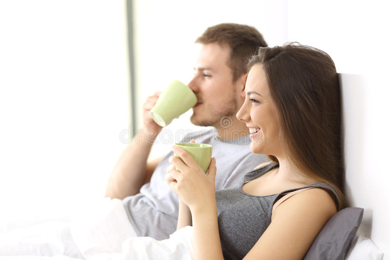 Relaxed couple having breakfast on the bed stock photos