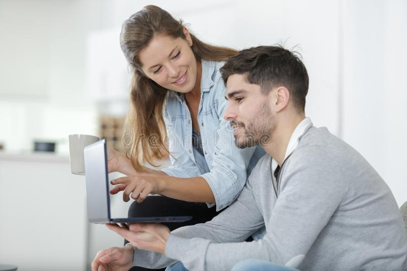 Relaxed couple looking at laptop in home royalty free stock photo