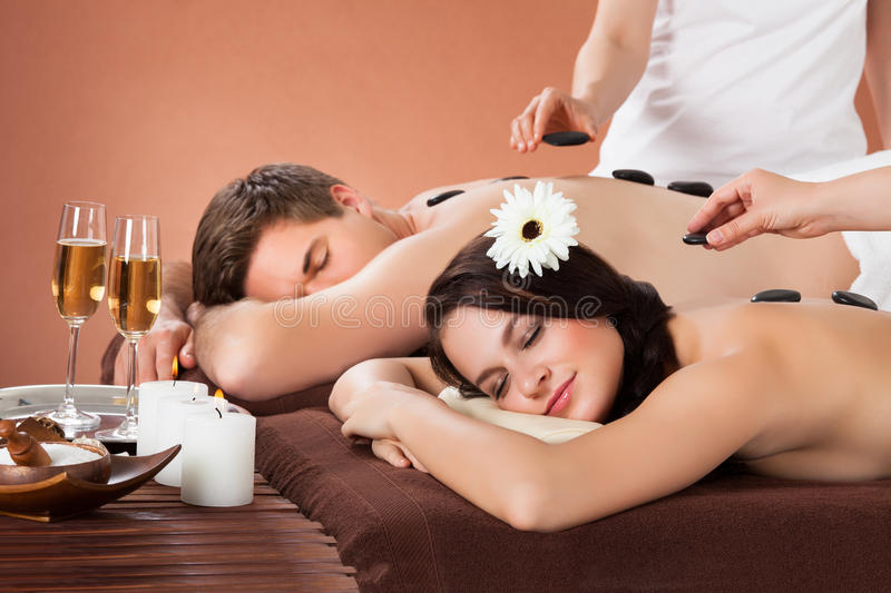 Relaxed couple receiving hot stone therapy at spa stock image