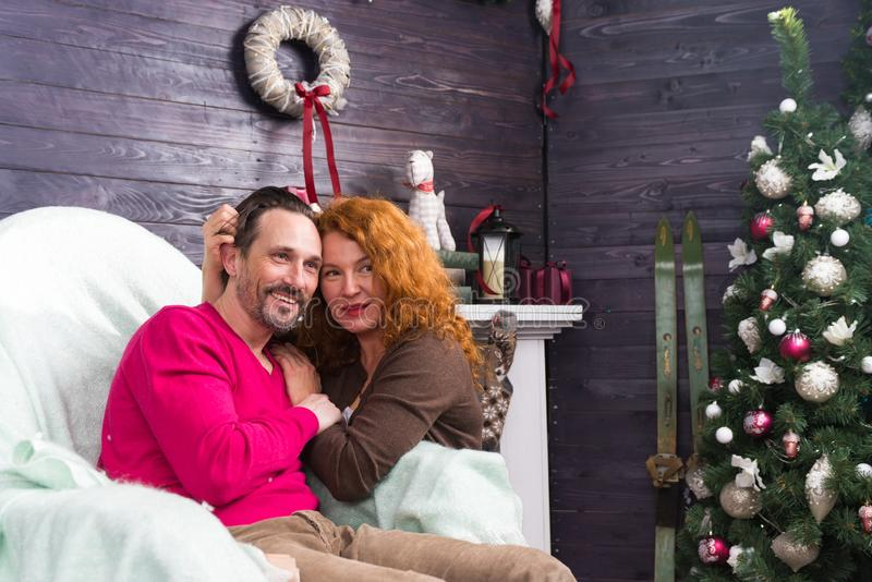 Relaxed couple smiling and looking into the distance during winter holidays. Young bearded men sitting in the armchair and smiling while his wife leaning to him stock photos