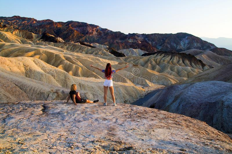 A Relaxed couple of travellers enjoying view of peaceful ancient eroded mountains landscape at Zabriskie Point, Death Valley USA. Travel men sitting and women royalty free stock photo