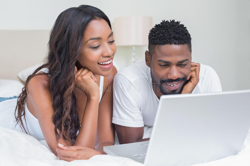 Relaxed couple using laptop on bed. At home in bedroom stock image