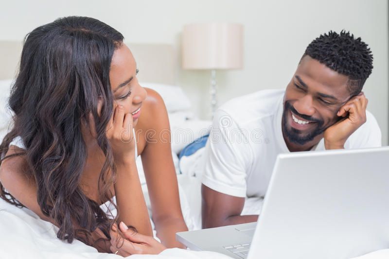 Relaxed couple using laptop on bed. At home in bedroom stock photo