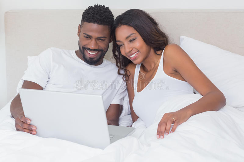 Relaxed couple using laptop in bed together. At home in bedroom stock photography