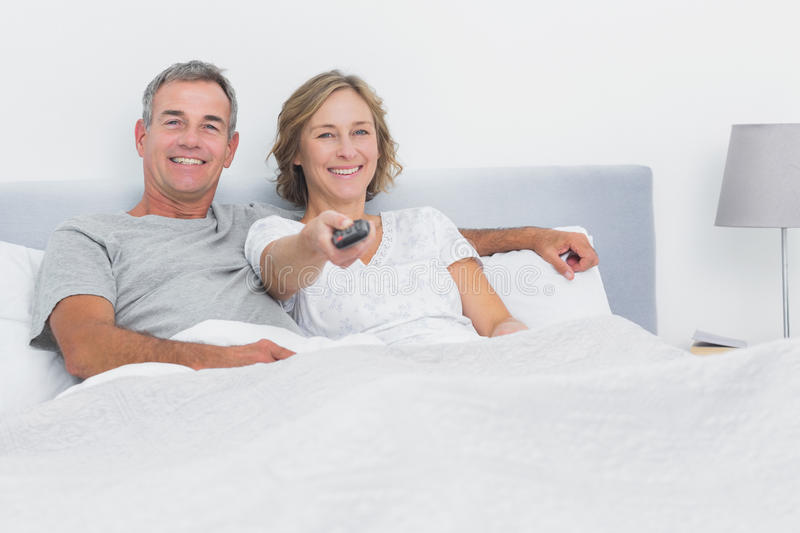 Relaxed Couple Watching Tv In Bed Looking At Camera Stock Photo
