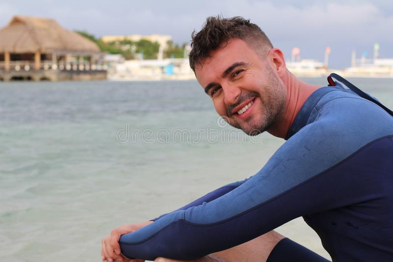 Relaxed cute man smiling at the beach royalty free stock photo