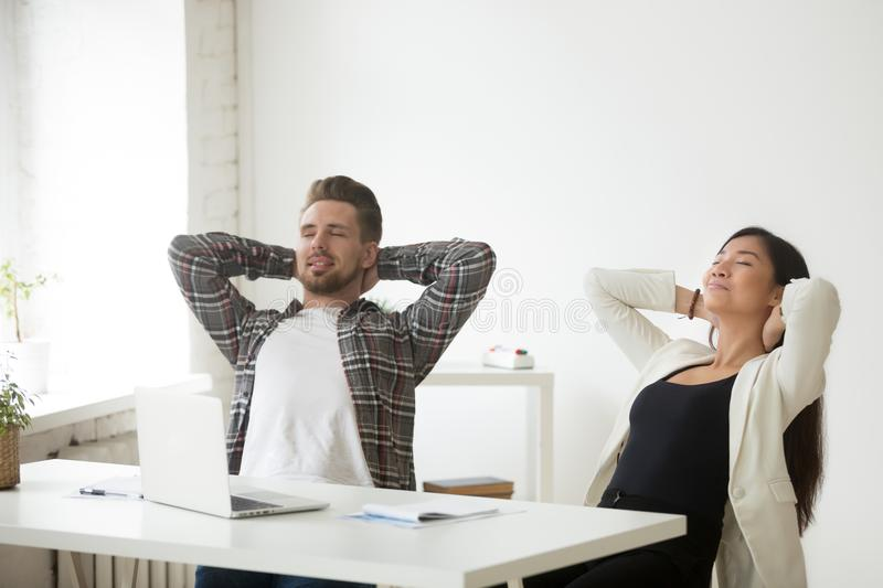 Relaxed diverse asian and caucasian colleagues enjoy break at wo. Relaxed asian and caucasian office colleagues enjoy break at workplace breathing fresh air stock photos