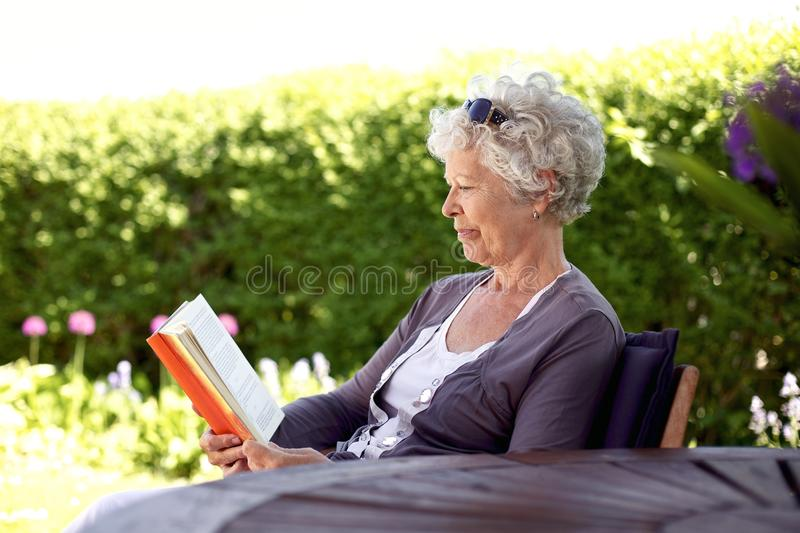 Relaxed elder woman reading book stock images