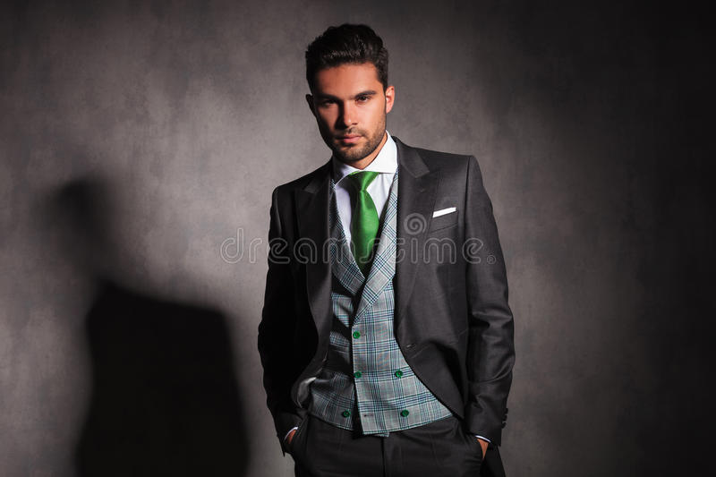 Relaxed elegant man with hands in pockets wearing tuxedo stock photos