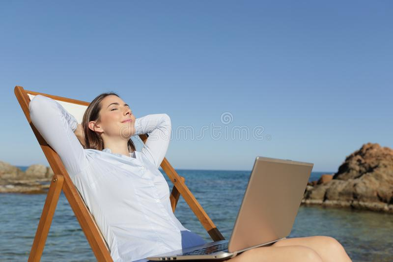 Relaxed entrepreneur resting on the beach with a laptop royalty free stock photo