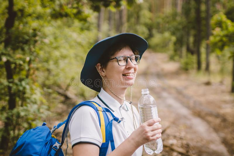 Relaxed female tourist resting in nature. Happy woman tourist with backpack. tourist girl drinking water in forest. Female with royalty free stock photos