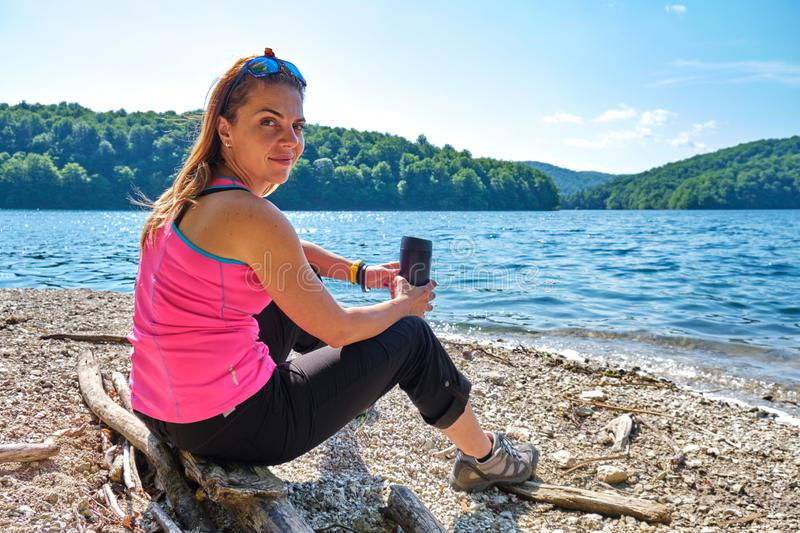 Relaxed female tourist with a thermal insulated coffee mug in hands, sitting down on a log at a mountain lake shore. Relaxed female tourist with a thermal stock image